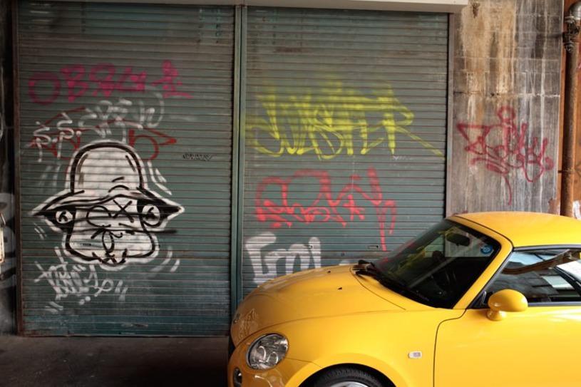 黄色い車とシャッターの落書き