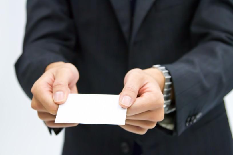 両手で名刺を渡すビジネスマン