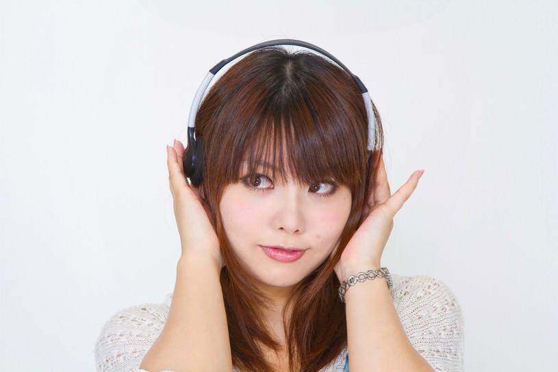 ヘッドフォンを耳に当てる女性