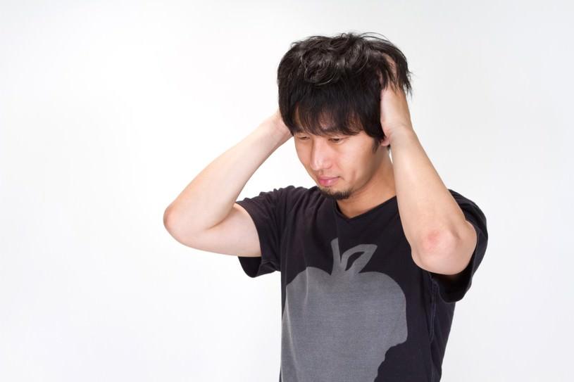 悩み、頭をかきむしる男性