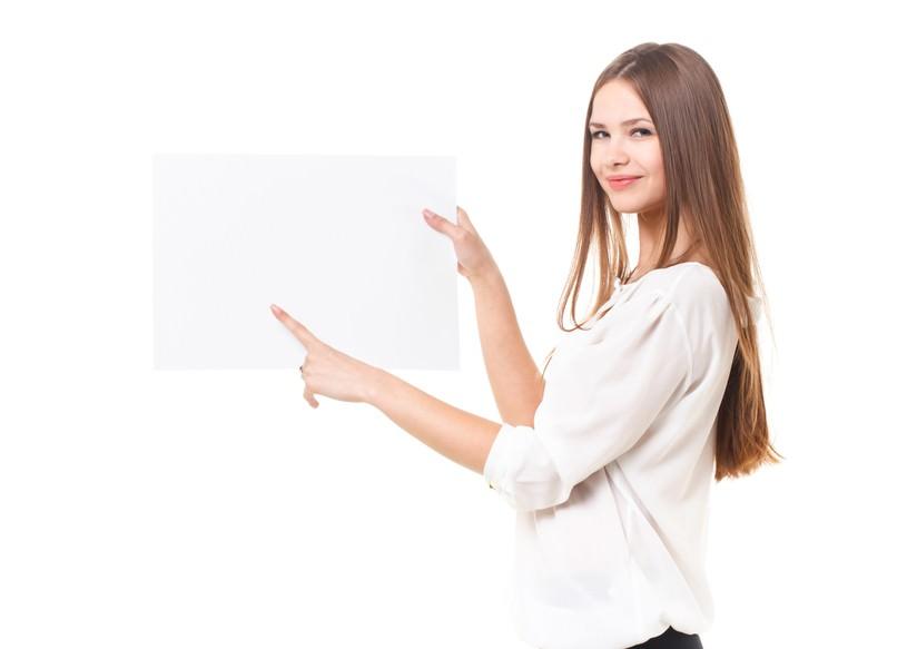 白いボードに指をさす外国人の女性