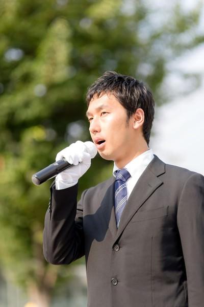 街灯演説するマイクを持った若い立候補者
