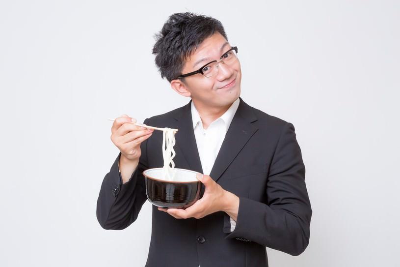 不味そうな素うどんをすくう素うどん面(ヅラ)のビジネスマン