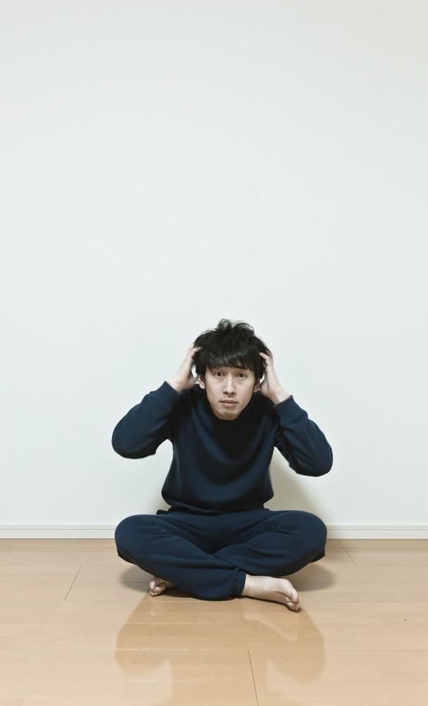 ワンルームで頭を抱える無職の男性。今後の不安と葛藤