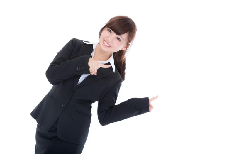 両手で指をさす案内係の女性
