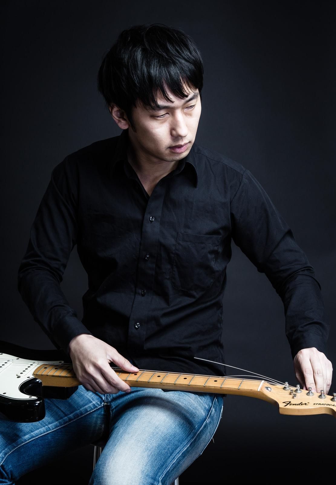 ギターの弦を張り替えるギタリスト松野氏(仮)ギターの弦を張り替えるギタリスト松野氏(仮) [モデル:大川竜弥]