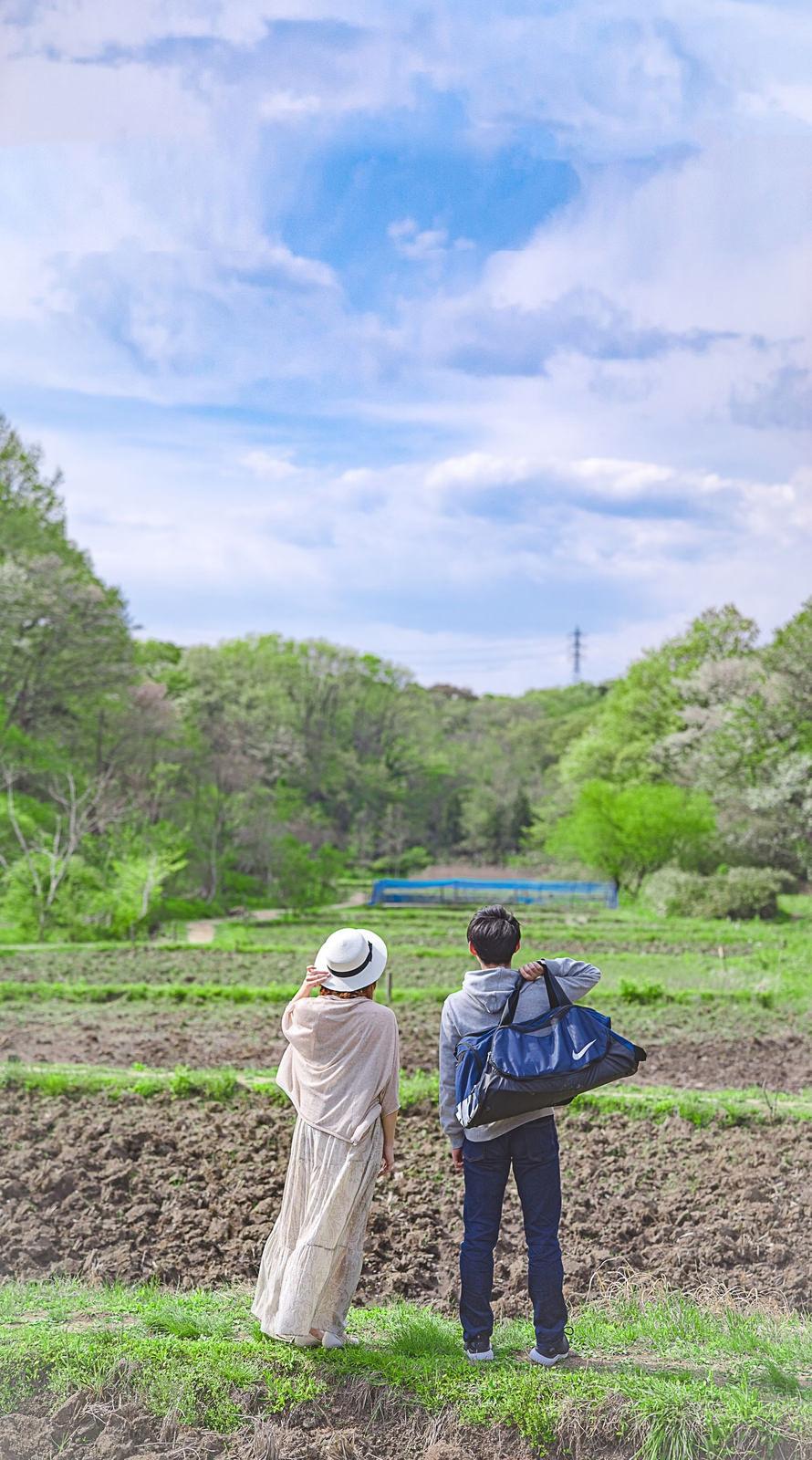 東京に就職が決まった彼と幼い頃によく遊んだ田んぼを眺める彼女のフリー素材