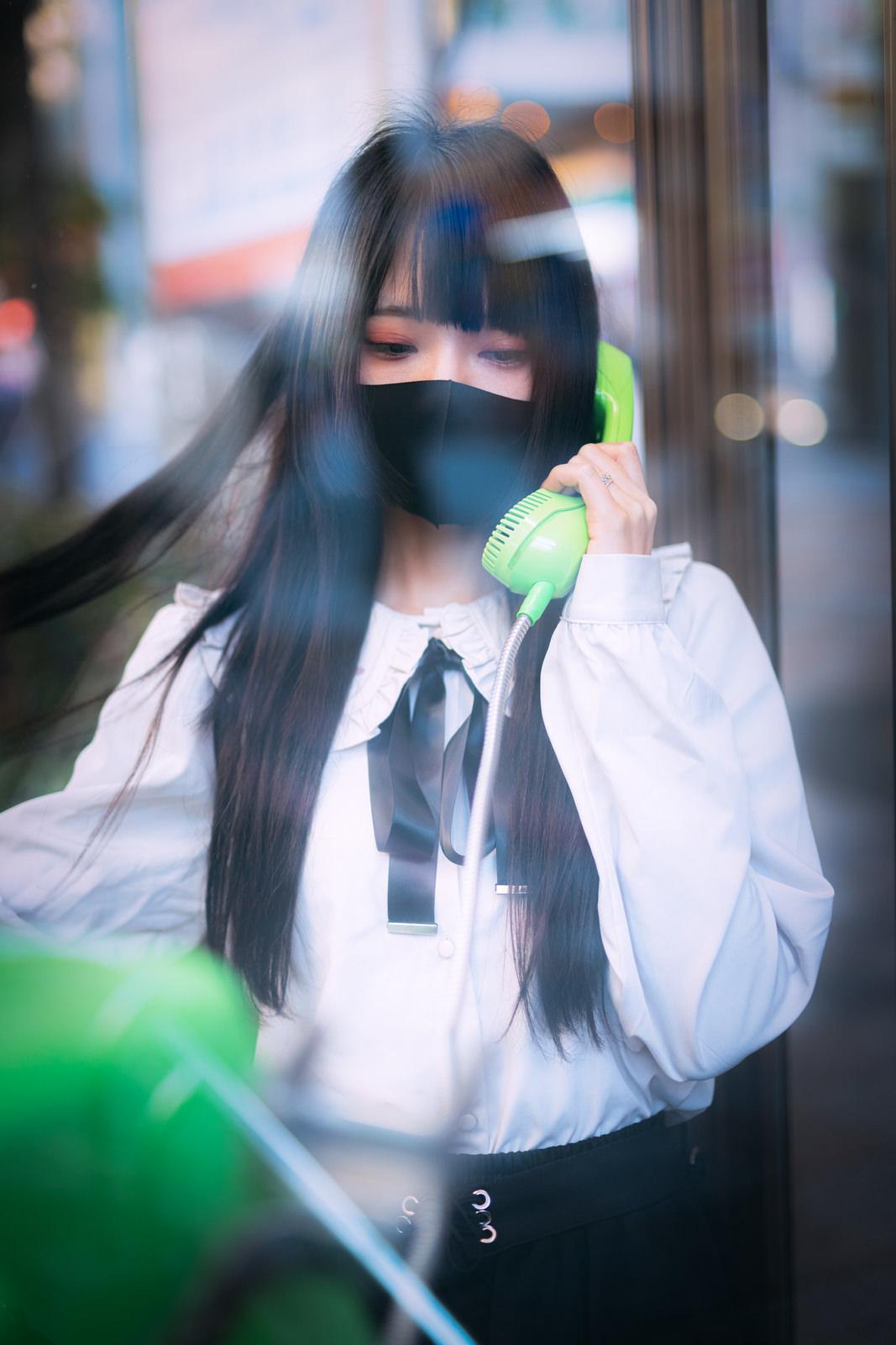 担当に連絡しても既読がつかないので公衆電話から電話する病みマスク女子のフリー素材