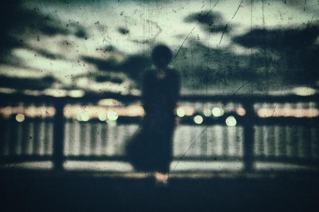 屋上のフェンスと黒い人影の写真
