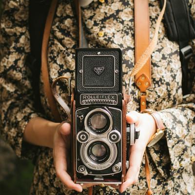 「オールドカメラを持つ女性の手」の写真素材