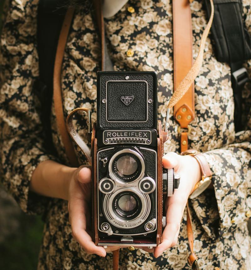 「オールドカメラを持つ女性の手」の写真