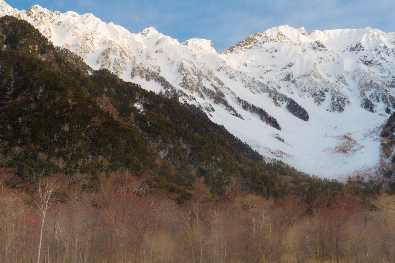「冬の上高地の透き通った空気の先にある穂高連峰」の写真