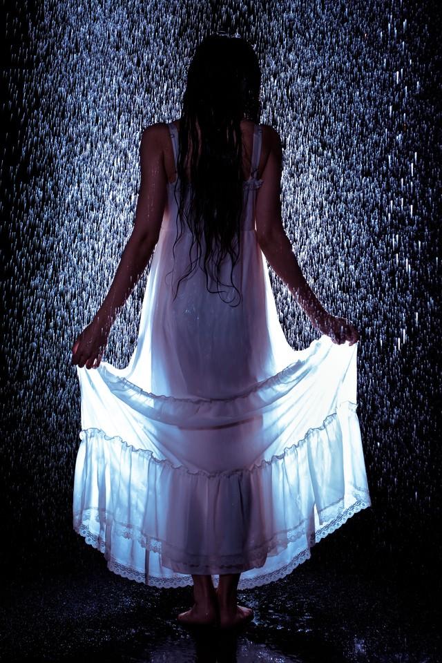 雨に濡れてワンピースの裾をあげる女性の後ろ姿の写真