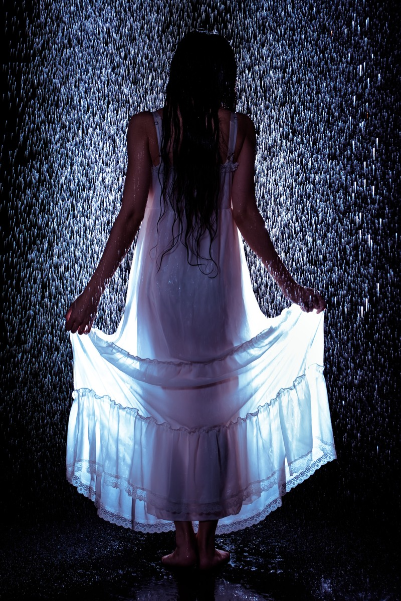 「雨に濡れてワンピースの裾をあげる女性の後ろ姿」の写真[モデル:緋真煉]