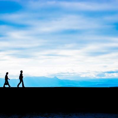 親子のシルエット(青空と埠頭)の写真