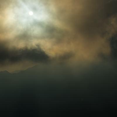 「北アルプスの曇天の中登山道を照らす満月」の写真素材