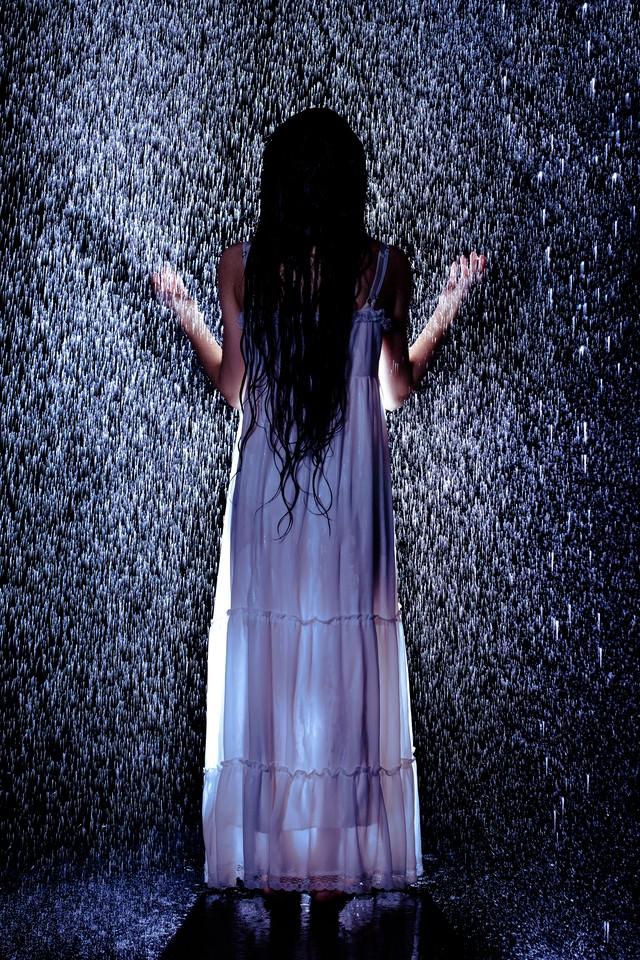 雨に打たれる女性の後姿の写真