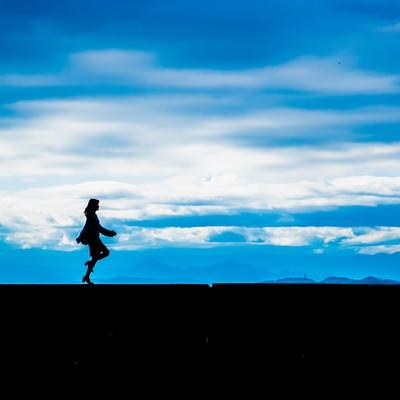 「軽やかなステップの女性のシルエット」の写真素材