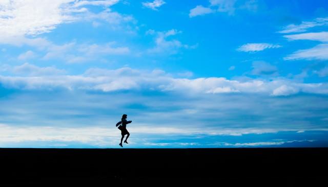 気分が舞い上がって飛び上がる女性のシルエットの写真