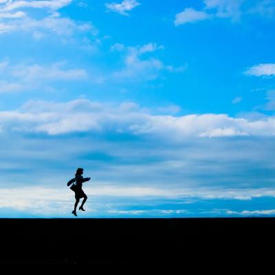 「気分が舞い上がって飛び上がる女性のシルエット」の写真素材