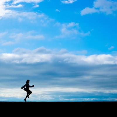 「バッグを持ってスキップしている女性のシルエット(青空)」の写真素材