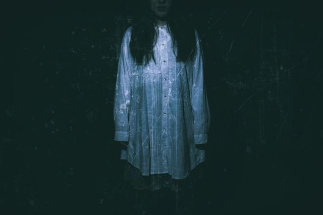 暗闇の中、立ちすくむ女性の姿の写真