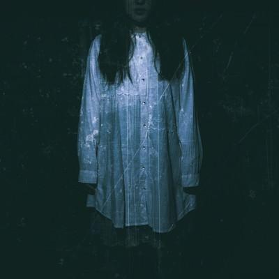 「暗闇の中、立ちすくむ女性の姿」の写真素材