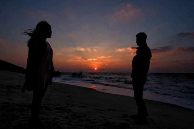 夕暮れの海辺と男女の写真