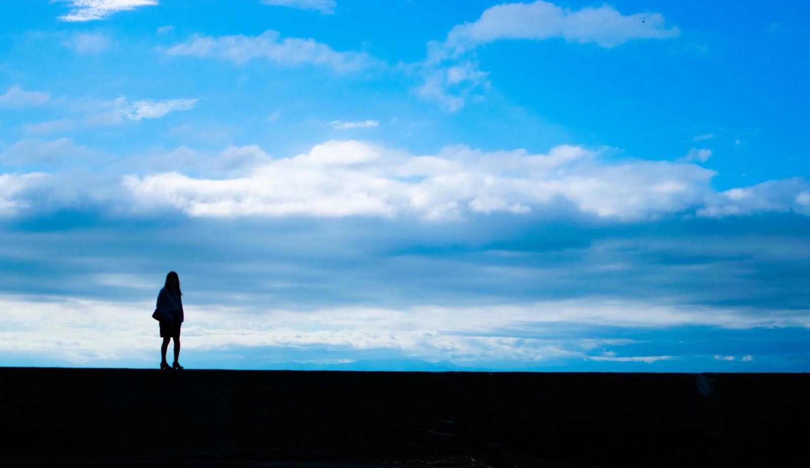 「目の前に広がる青空と女性の後ろ姿(シルエット)目の前に広がる青空と女性の後ろ姿(シルエット)」のフリー写真素材を拡大