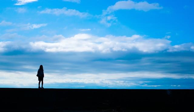 目の前に広がる青空と女性の後ろ姿(シルエット)の写真