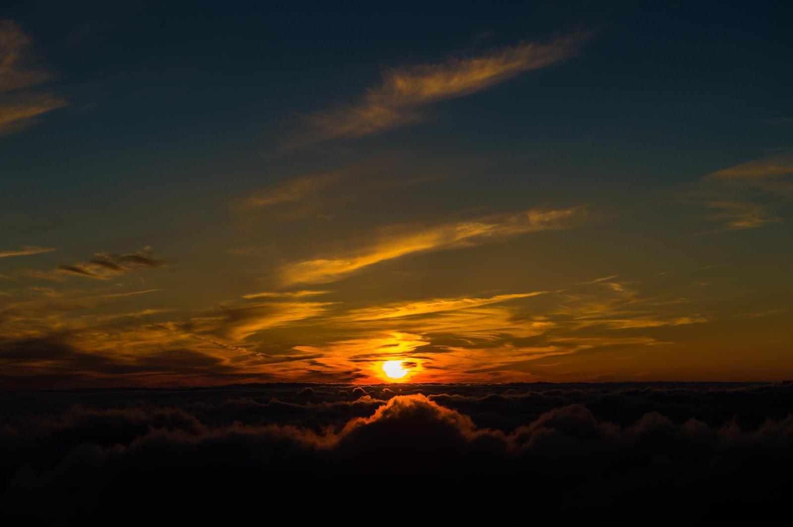「北アルプス日没直前に煌々と光を放つ太陽」の写真