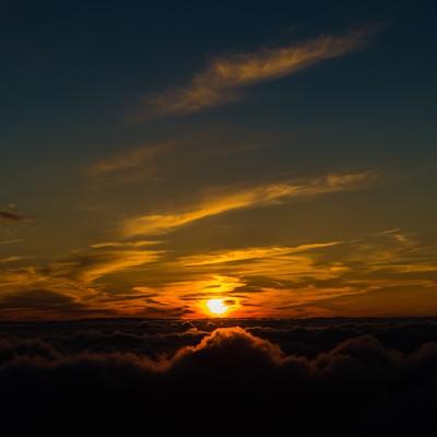 「北アルプス日没直前に煌々と光を放つ太陽」の写真素材