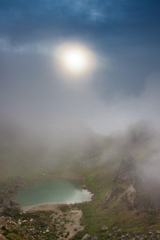 霧の中の焼岳の正賀池と日暈の写真