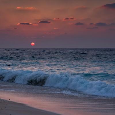 夕焼けと与論島の海と砂浜の写真