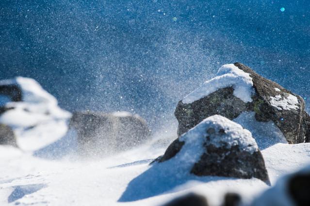 厳冬期の山で舞い上がる雪の粒子の写真