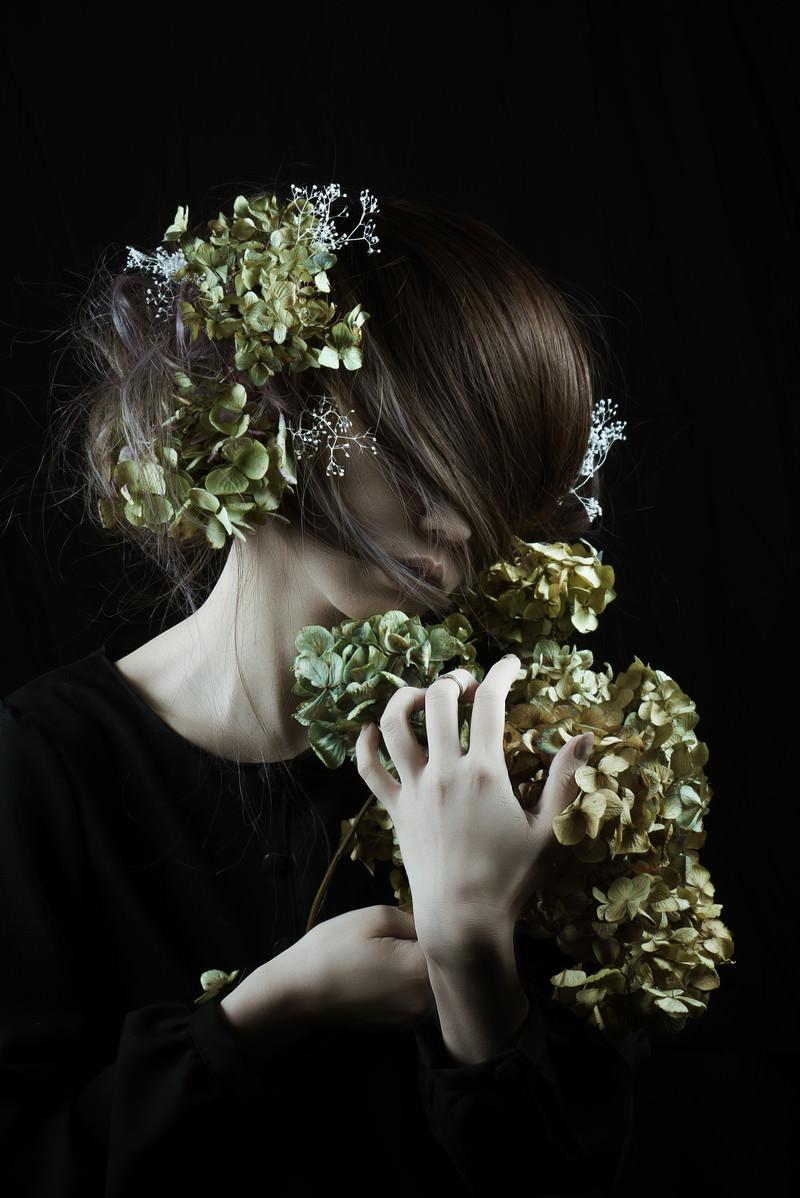 「モスグリーンの髪飾りを持つ女性と造花」の写真
