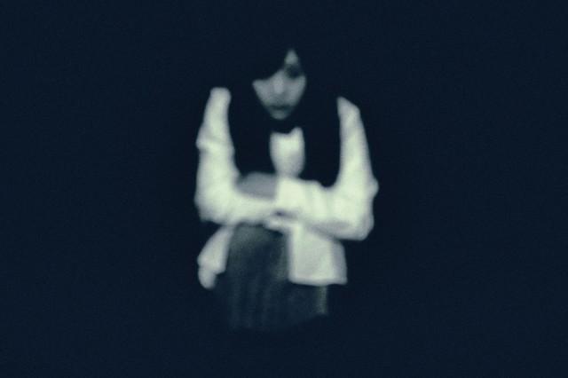 暗闇からこちらを見つめる女性の写真