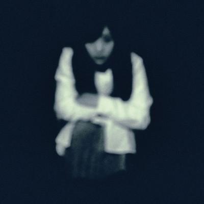 「暗闇からこちらを見つめる女性」の写真素材