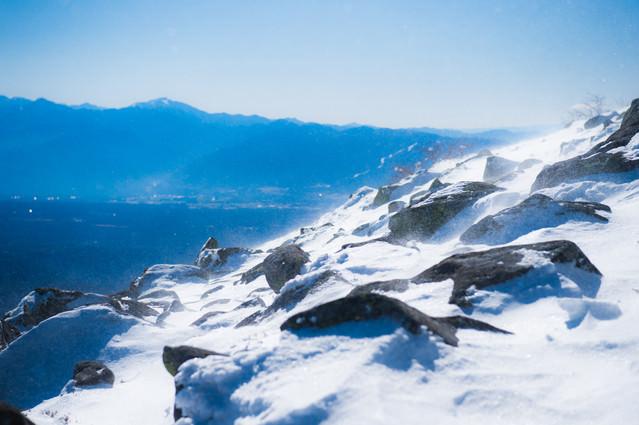冬山山頂の煌めく雪と岩の写真
