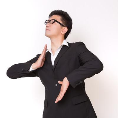 「不思議な踊りをはじめたスーツ姿の眼鏡男子」の写真素材