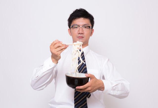 不味そうな伸びきった素うどんを食べる素うどんの写真