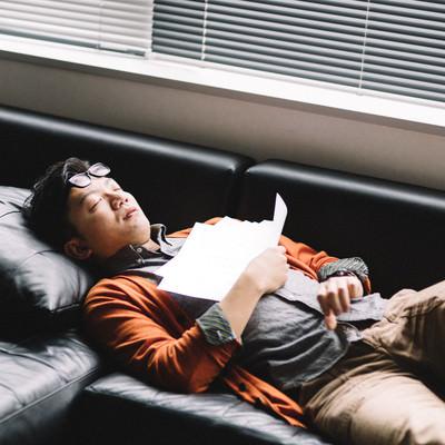 「ソファの上で死んだように眠る社畜」の写真素材
