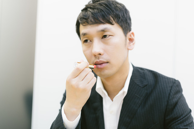 新製品を試す化粧品会社の男性社員の写真