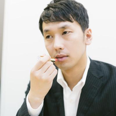 「新製品を試す化粧品会社の男性社員」の写真素材
