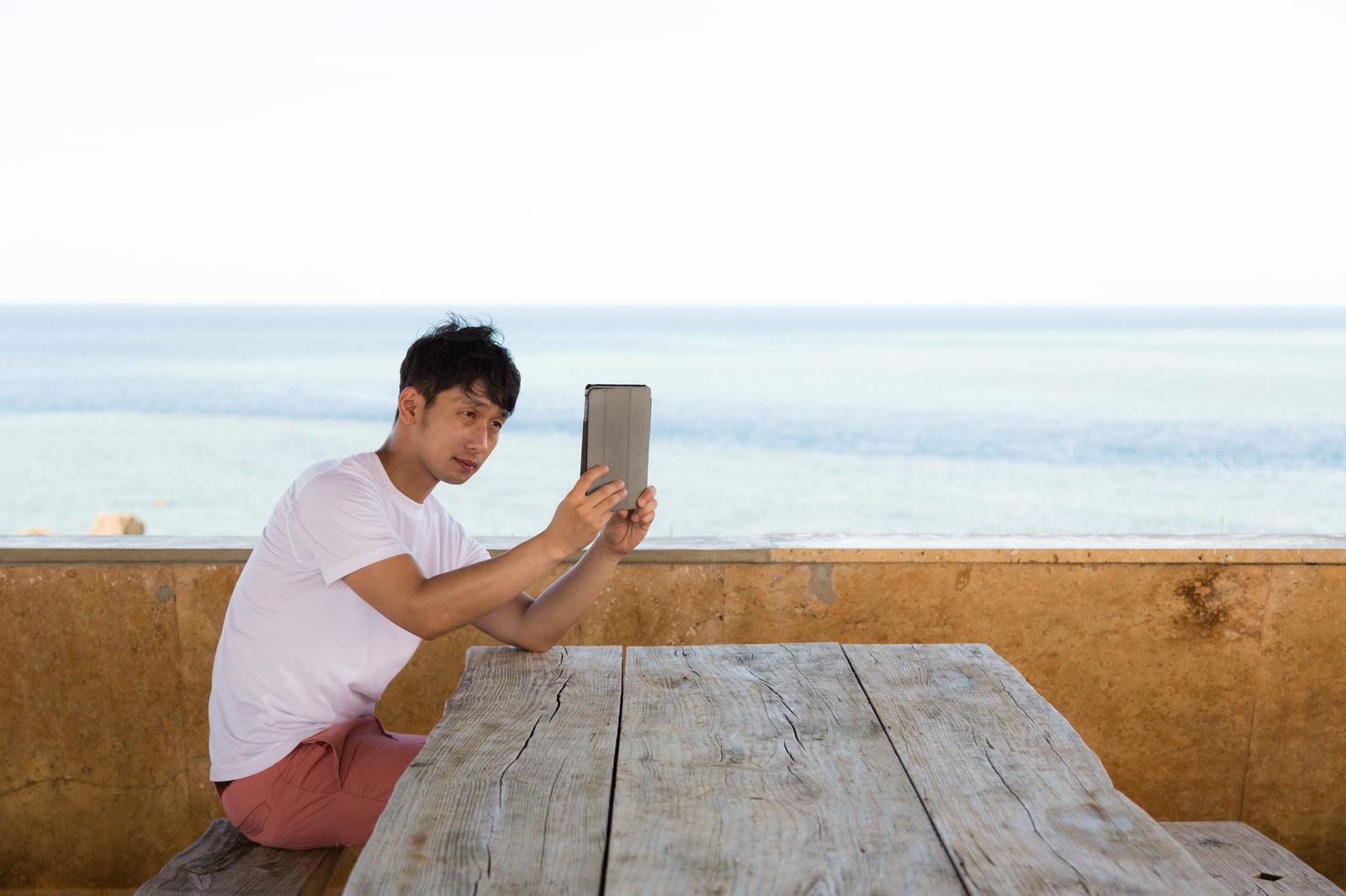 「タブレット端末で自撮りをする丘サーファータブレット端末で自撮りをする丘サーファー」[モデル:大川竜弥]のフリー写真素材を拡大