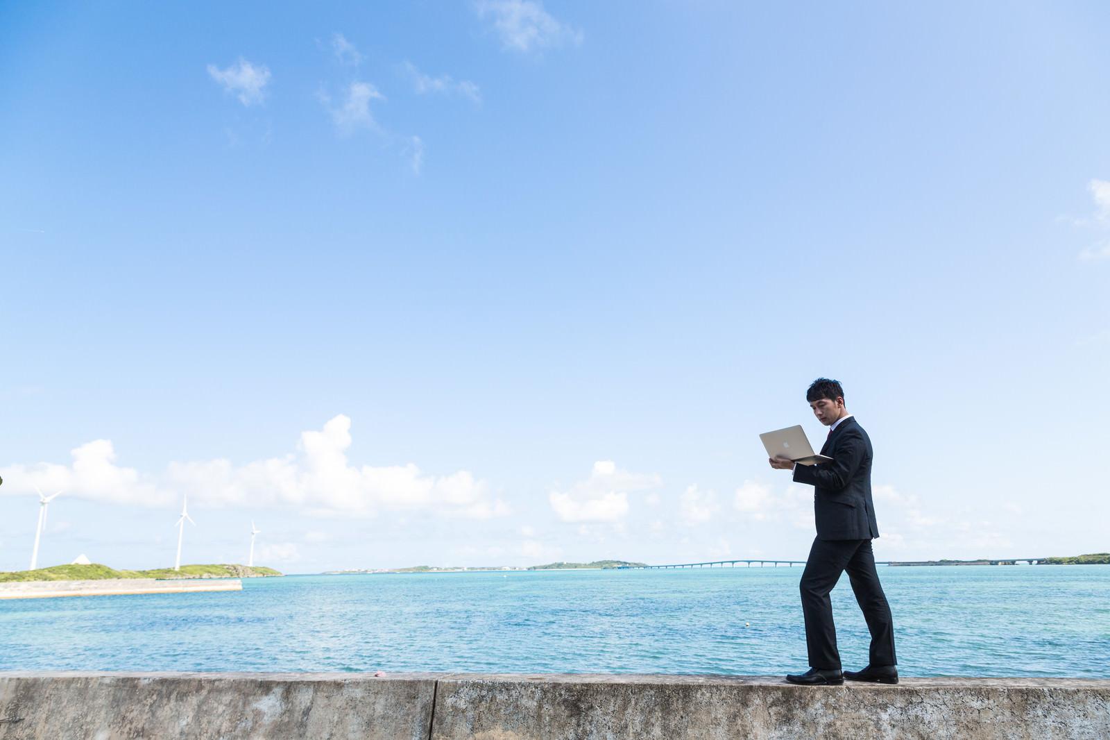 「南の島で電波を求めて歩くポケットWi-Fiトラベラー」の写真[モデル:大川竜弥]