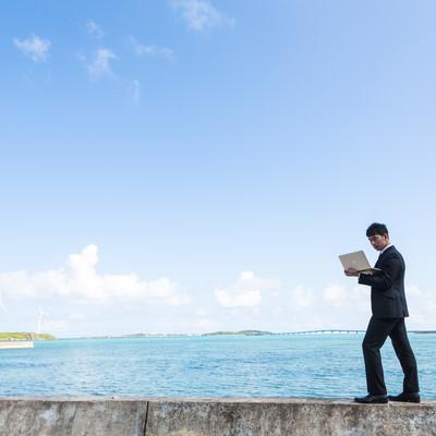 「南の島で電波を求めて歩くポケットWi-Fiトラベラー」の写真素材