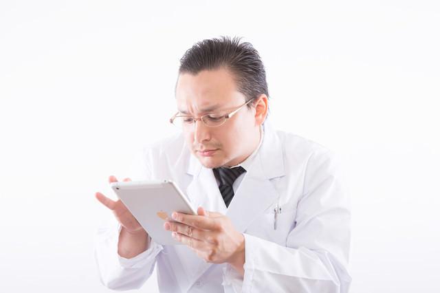 電子カルテに慣れていない白衣のお医者さんの写真