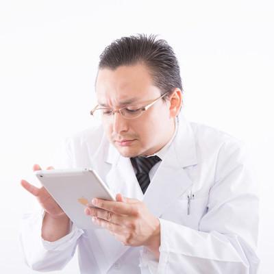 「電子カルテに慣れていない白衣のお医者さん」の写真素材