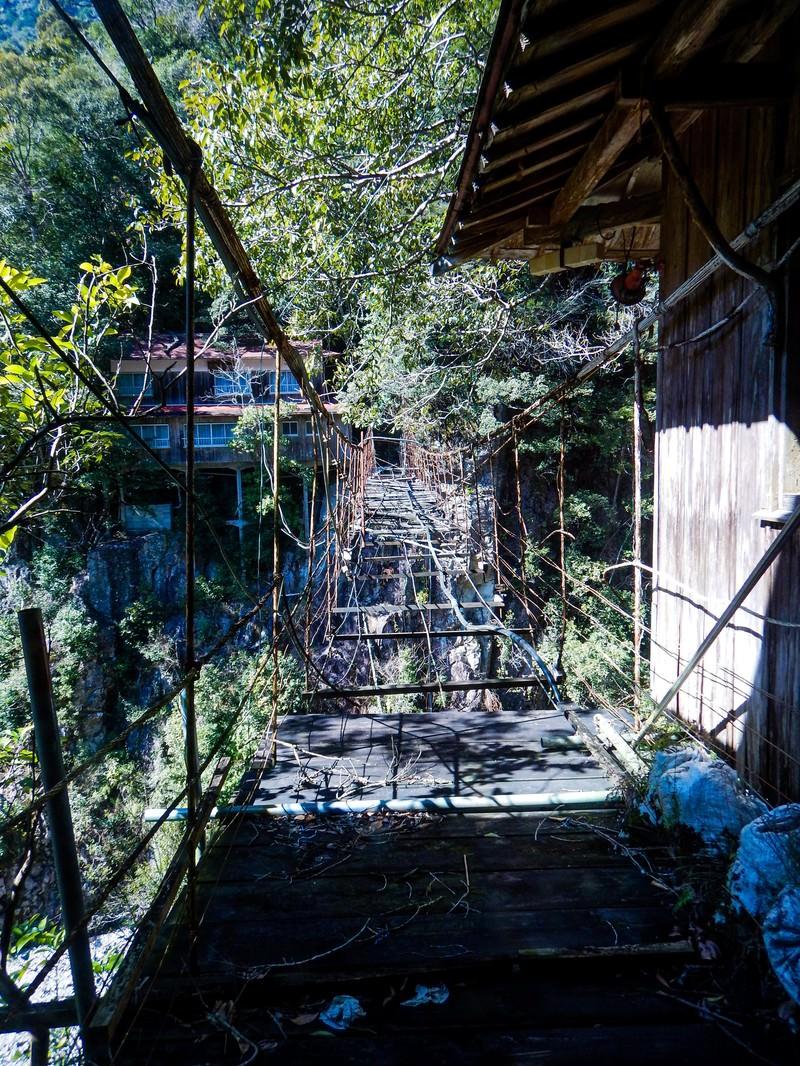「廃墟となった旅館へ続くボロボロの吊り橋」の写真